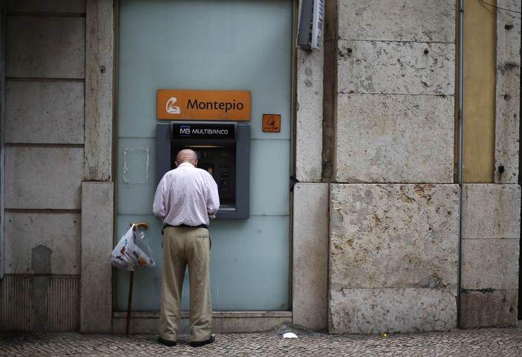 Een man pint geld in Lissabon. Beeld reuters