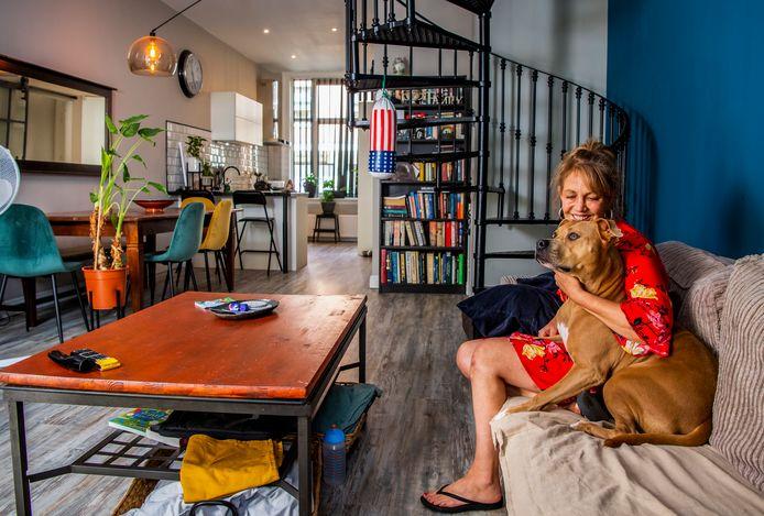Tina Ortiz in haar woonkamer met hond Cashew, met achter zich de trap die haar een doorn in het oog is.