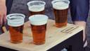 Vier bier in plastic wegwerpbekers
