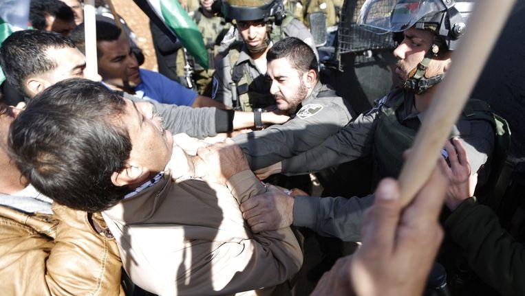 Een Israëlische grenswacht grijpt minister Abu Ein bij zijn keel, tijdens een demonstratie die vandaag in de buurt van Ramallah werd gehouden. Beeld afp