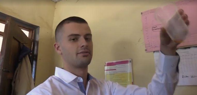 Een still uit de video over een zogenaamde malariakuur. Sam Little houdt een schenkkannetje omhoog met bleekmiddel dat hij als medicijn gebruikt.  Beeld Brighteon