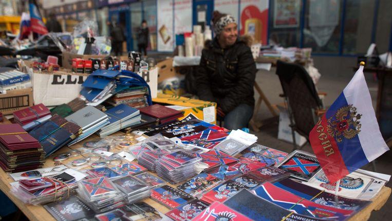 Een straathandelaar in DOnetsk verkoopt Russische parafernalia Beeld AFP
