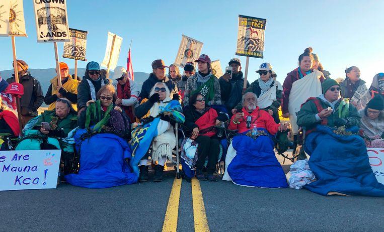 Demonstranten blokkeren de weg naar Mauna Kea, Hawaii, om te protesteren tegen de bouw van een reuzentelescoop. Beeld AP