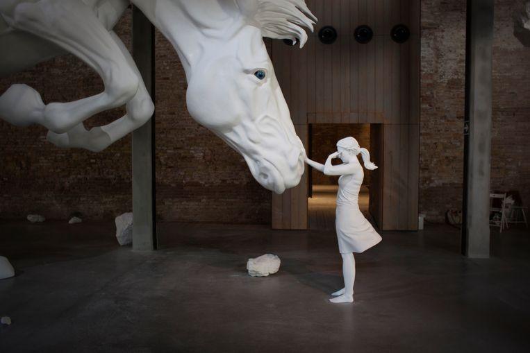 Een gigantisch wit paard vult het Argentijnse paviljoen tot aan de zoldering. Rotsblokken hangen in de lucht. Daarbij vergeleken zijn de levensgrote beelden van een man en vrouw klein. Een installatie van Claudia Fontes. Beeld TRBEELD