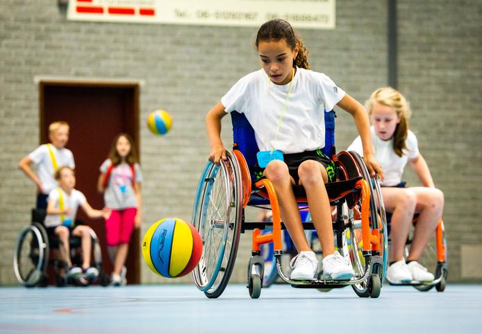 Leerlingen sporten vandaag in rolstoelen in sporthal de Schenkel.
