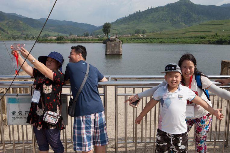 Chinezen kijken naar Noord-Korea vanaf de Hekou Broken Bridge Beeld Ruben Lundgren