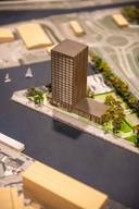 Maquette geplande woontoren met onderin een hotel, onderin een houten blokje dat appartementencomplex de Sluiswachter verbeeldt.