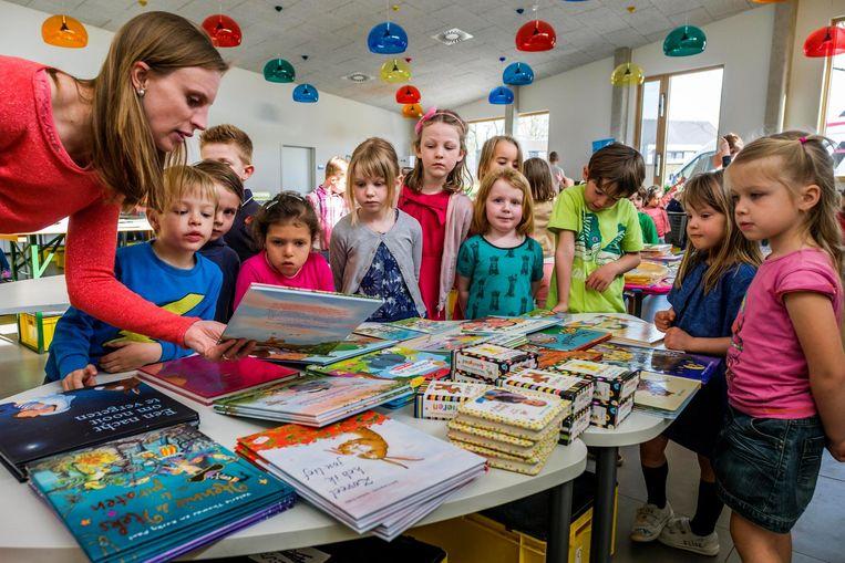 De kinderen komen bekijken welke boeken ze het leukst vinden.