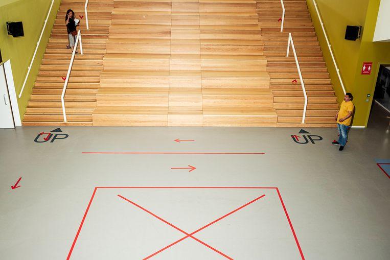 De afgeplakte hal en grote trap in het Cburg College. Beeld Jakob Van Vliet