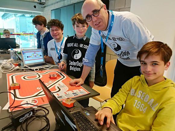 Enkele cursisten en vrijwilligers bij de telegeleide robotjes.