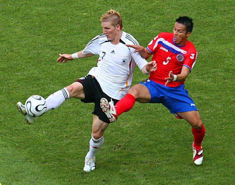 Bastian Schweinsteiger in duel met Gilberto Martinez. 'Schweini' werkte de openingsmatch af in zijn toenmalige thuishaven: de Allianz Arena in München.