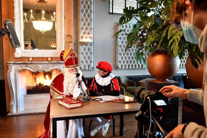 Sinterklaas en roetveegpiet bij het haardvuur terwijl hij aan het bellen is met Bruls. Omroep RN7 maakt opnames.