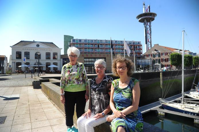Trude Waasdorp, Ineke Weug en Tanja Snijders (van links naar rechts) van Comité Vlissingen Beschermd Stadsgezicht aan de Zeilmarkt, met op de achtergrond het Arsenaalplein met Carrousel en galerijflat.