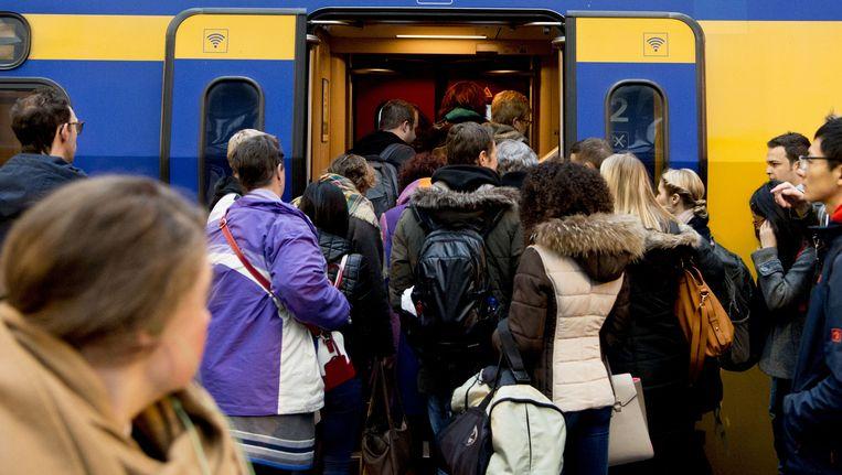 Reizigers stappen in de spits op de trein op Rotterdam Centraal. Beeld anp