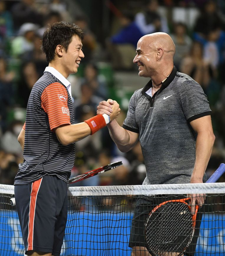 Kei Nishikori (L) schudt de hand van Andre Agassi (R). Beeld afp