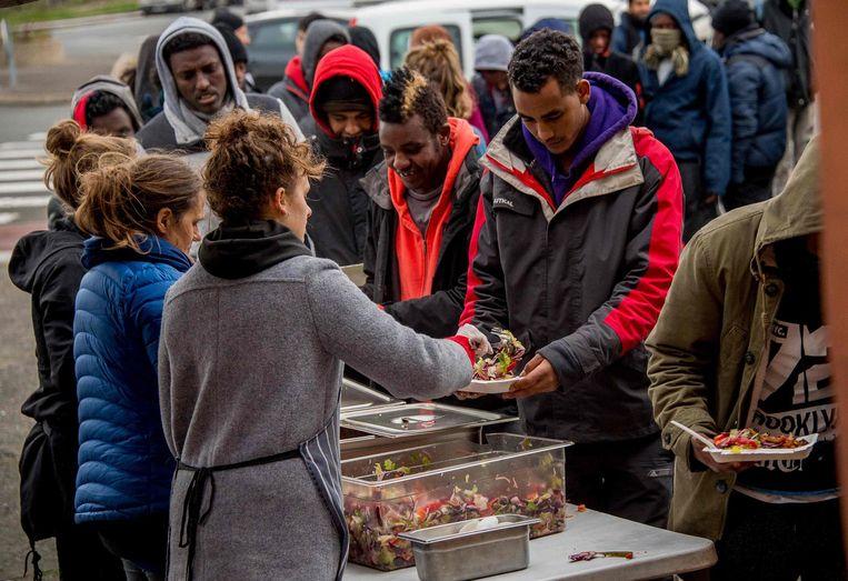 Vrijwilligers delen eten uit aan migranten bij Calais Beeld afp