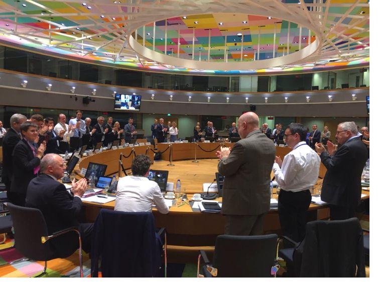 Jeroen Dijsselbloem (zittend, midden, wit overhemd) heeft op 4 december voor het laatst als voorzitter de vergadering van de ministers van financiën toegesproken. Hij krijgt een staande ovatie.  Foto: Michel Reijns Beeld rv
