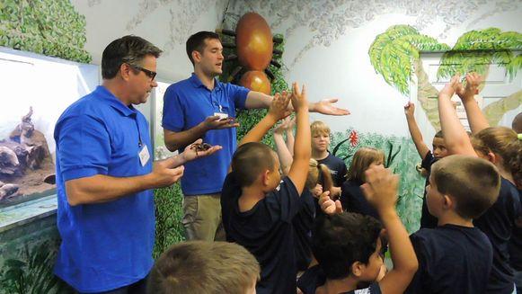 John Cambridge (R) en een collega tonen spinnen tijdens een schooluitstapje.
