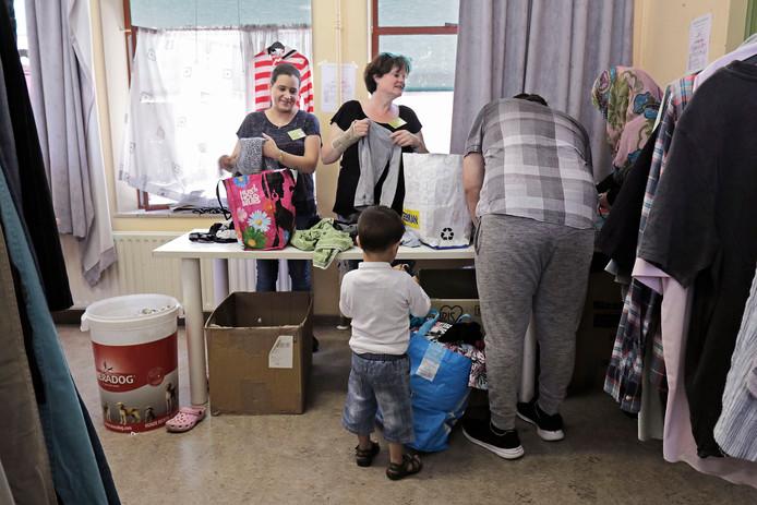 Oss Vanessa (links) en Rian (rechts) kleding vouwend tijdens de laatste kledinguitgifte van Stichting Helpende Handen in 't Hageltje.