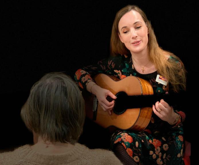 Muziektherapeut Annemarie Kosse zingt en speelt gitaar voor Mieke op de afdeling dementie van ouderenorganisatie Van Neynsel in Den Bosch.