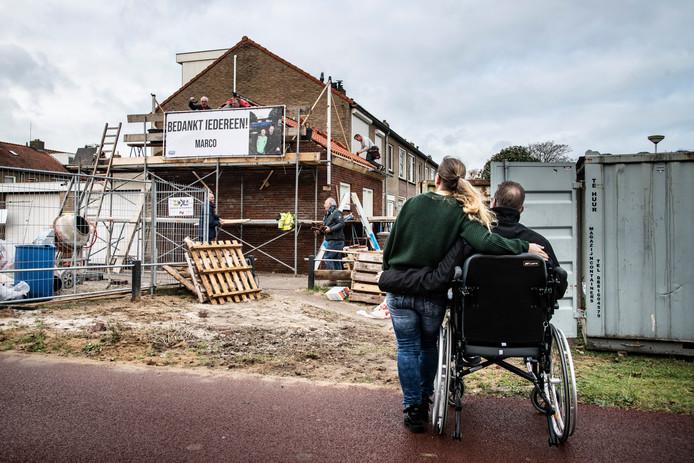 Marco en zijn vrouw Debby kijken naar de vrijwilligers die druk zijn met het realiseren van de aanbouw aan zijn huis.