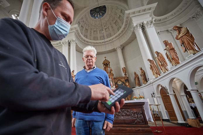 Gerard Claassen (midden) kijkt toe hoe Ralf van Veghel (voorgrond) het carillon op afstand instelt in de kerk van Erp.