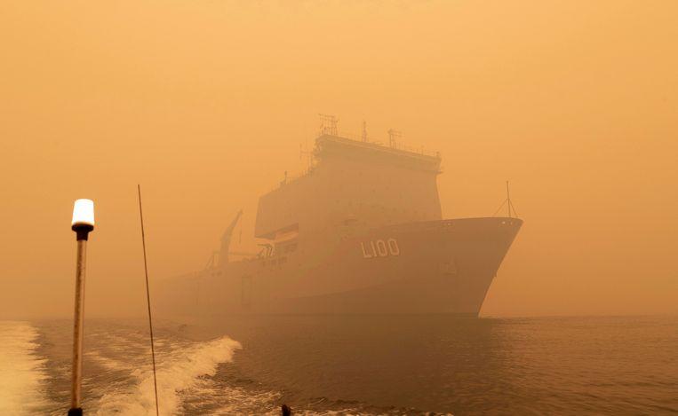 De HMAS Choules voor de kust van Mallacoota, in een dikke rookwolk als gevolg van de branden.  Beeld AP/Ministerie van Defensie Australië