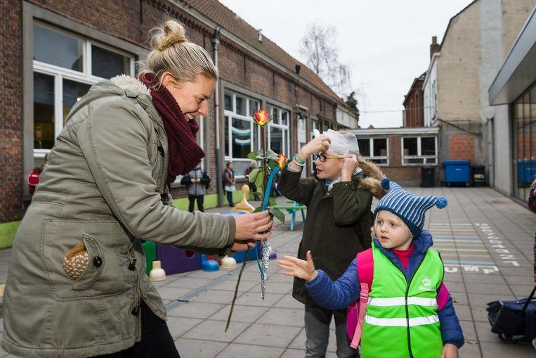 Sara-Elise (4) geeft een bloemetje aan de juf om haar een hart onder de riem te steken.
