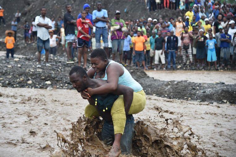 Een man draagt een vrouw over een rivier waar de brug is ingestort, bij Port-au-Prince, Haïti Beeld afp