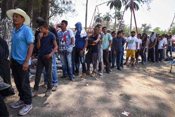 Deelnemers aan de mars wachten in het zuiden van Mexico op een maaltijd.