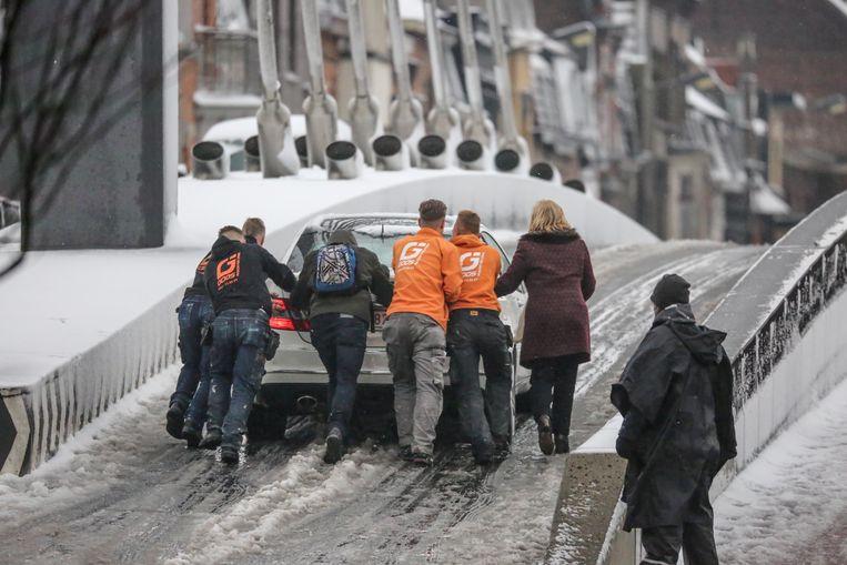 Een auto raakt niet boven op de Noordbrug in Kortrijk. Enkele sterke mannen van de firma Goos liepen er naartoe en duwden hem de brug op.