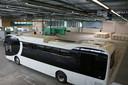De eerste elektrische BYD-bussen worden in een hal in Hengelo opgeladen en rijklaar gemaakt.