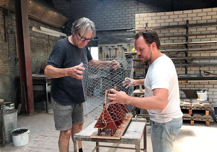Léon Vermunt  en Ruben Van de Ven (rechts) bezig met het maken van de eerste gietmallen voor het kunstwerk d' Ouwe Sok van Roosendaal.