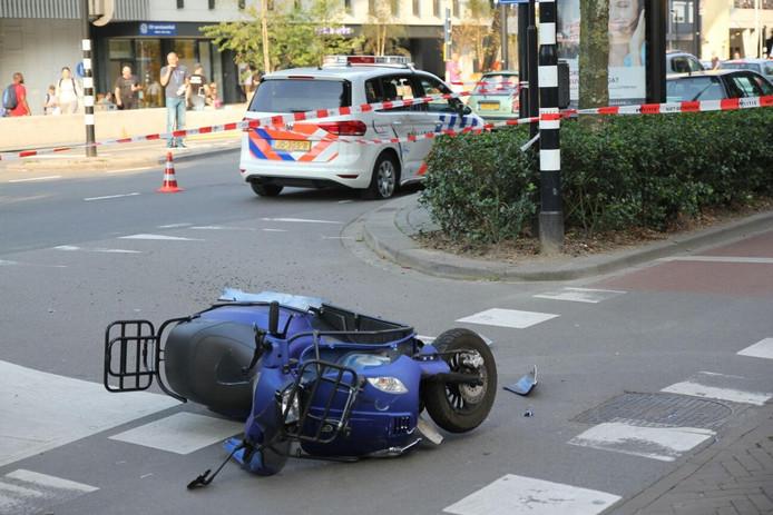 De gecrashte scooter met op de achtergrond de geraakte politiewagen.