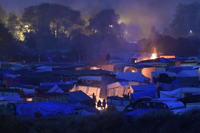Migranten warmen zich aan een vuurtje op de tweede ochtend van de evacuatie.