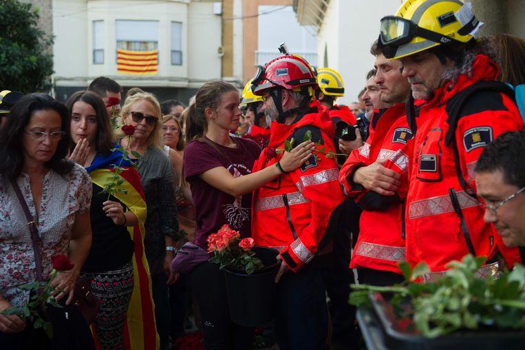 Een Catalaanse vrouw omhelst een brandweerman op de dag van het referendum. Anderen staan in de rij om bloemen op de stembussen te leggen. Beeld AFP