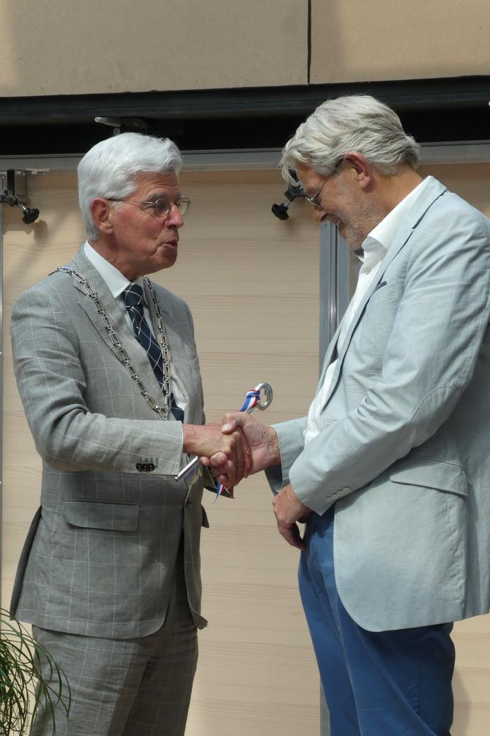Jan Pommer (links) overhandigt de sleutel aan Rien Schakenraad, voorzitter van de Stichting De Meander.