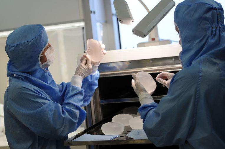 Franse technici controleren siliconen borstimplantaten. Beeld AFP