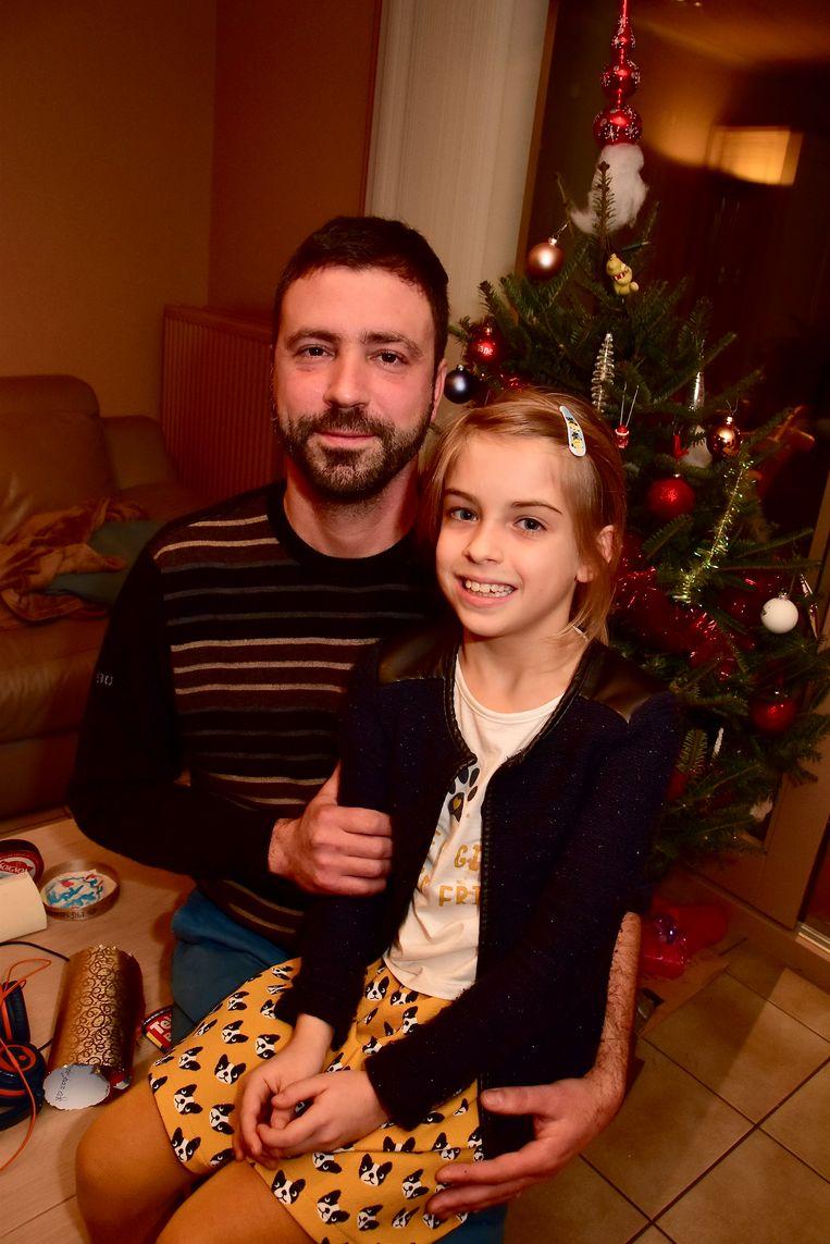 """Postbode Mike Bellens met zijn dochtertje Ine (8) voor de kerstboom. """"Een mirakel dat ik dit overleefd heb."""""""