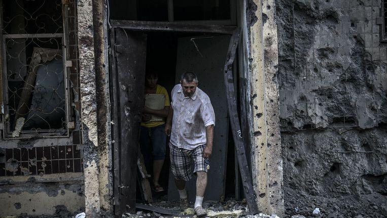 Mensen komen uit hun huis na een granaataanval in Donetsk. Beeld afp