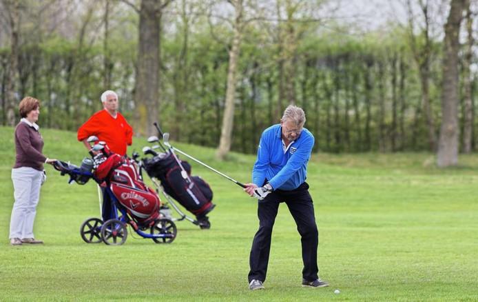 Kees de Roover aan slag met op de achtergrond Jolanda Mallens en Harrie Bongartz tijdens het golfkampioenschap bij Princenbosch. foto Johan Wouters/het fotoburo