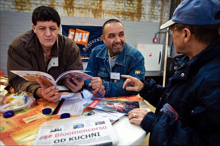 Een medewerker van de FNV (M) in gesprek met Poolse arbeiders op de Poolse Banenbeurs in de Westergasfabriek in Amsterdam. Beeld ANP