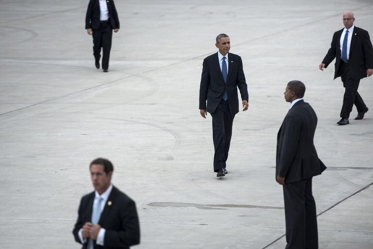 President Obama loopt in 2014 op de luchthaven van Gary in de staat Indiana  naar Air Force One terwijl agenten van de Secret Service hem beveiligen. Sinds president Roosevelt levert Boeing de presidentiële vliegtuigen. Beeld AFP