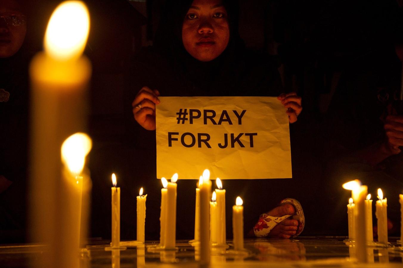 Een Indonesische moslima houdt een blad vast met de tekst #pray for Jakarta.