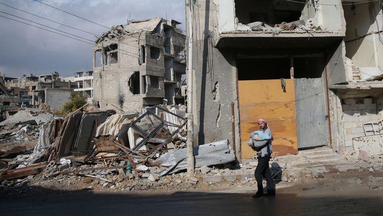 Een man met een baby staat voor een verwoest huis in de Syrische stad Douma. De stad is in handen van rebellen. Beeld REUTERS