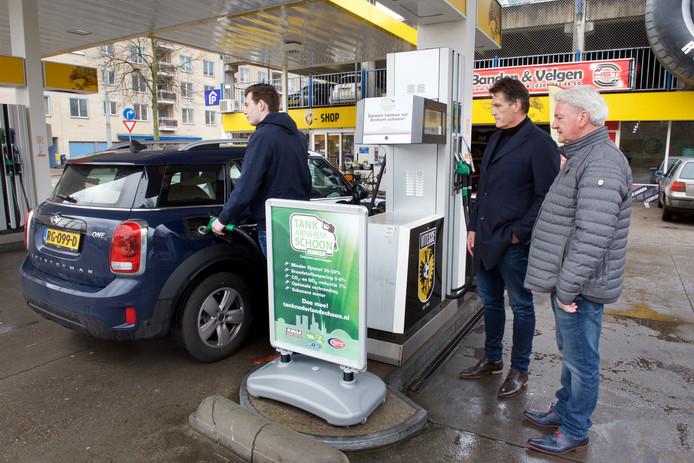 Boudewijn Sanders (m) en Marius Overbeeke (r) kijken toe terwijl een klant XMILE tankt in Arnhem.