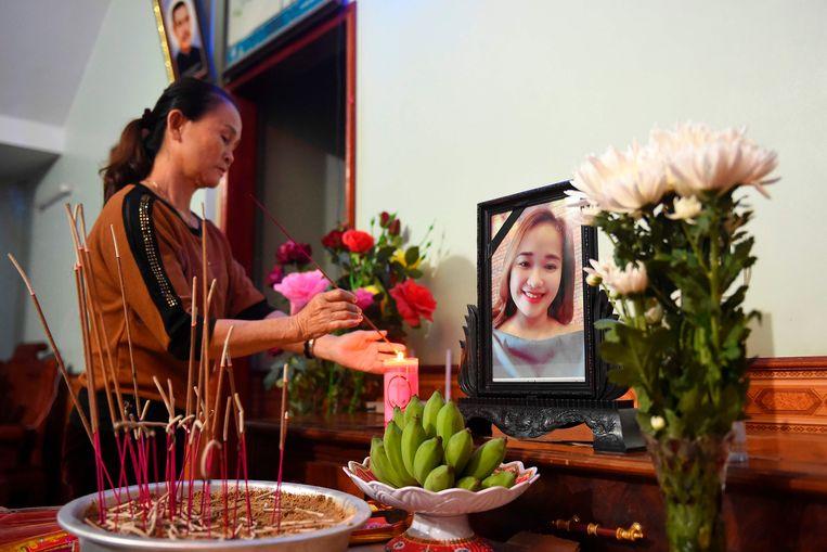 Een moeder van een vermoedelijk slachtoffer steekt een kaars aan bij een portret van haar vermiste dochter.