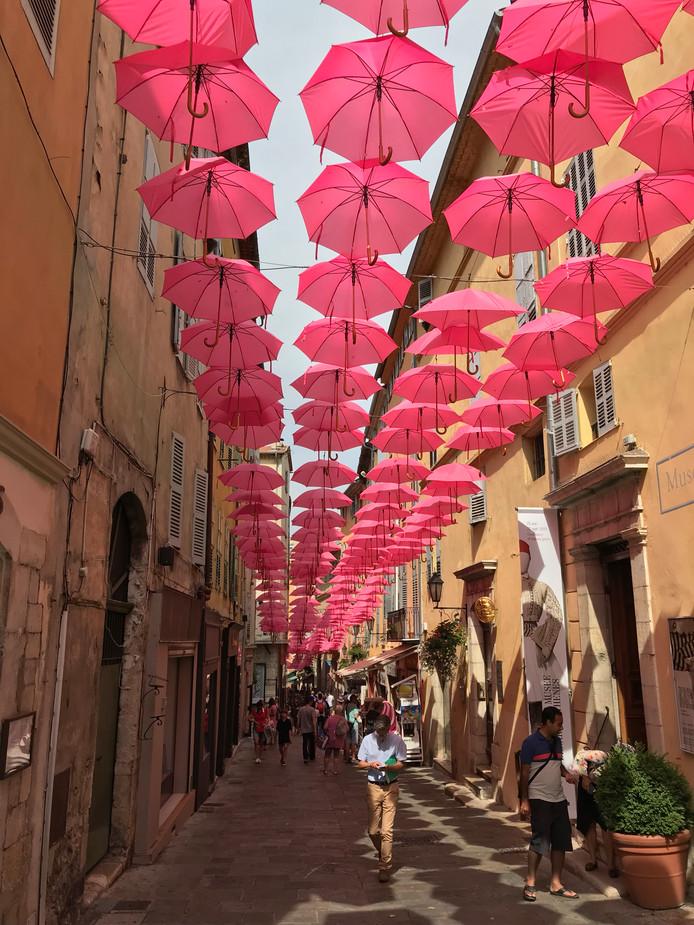 Ook in parfumstad Grasse in Frankrijk wordt er verkoeling geboden door middel van paraplu's. Het kleurt de straat ook mooi roze.