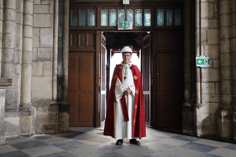 De aartsbisschop van Parijs, Michel Aupetit, arriveert in een onaangetast deel van de kathedraal voor een ceremonie ter ere van Goede Vrijdag. Beeld AFP