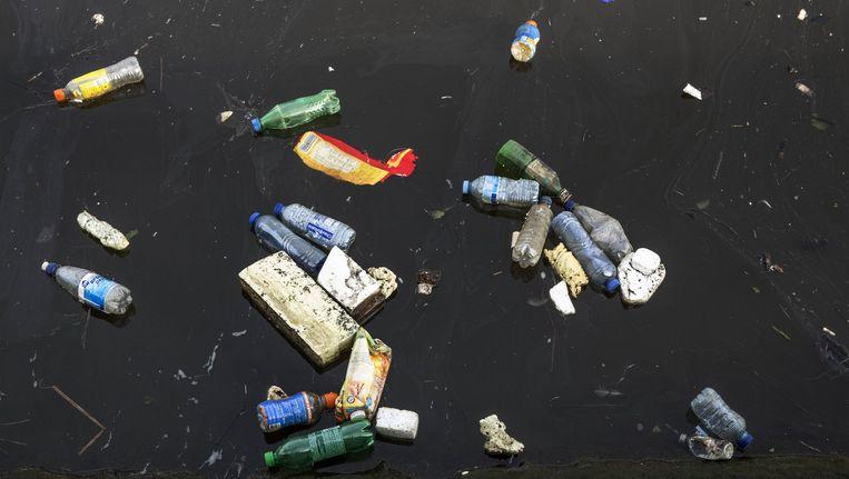 Plastic flessen en ander zwerfaval in de Amsterdamse gracht. Beeld Marco Okhuizen